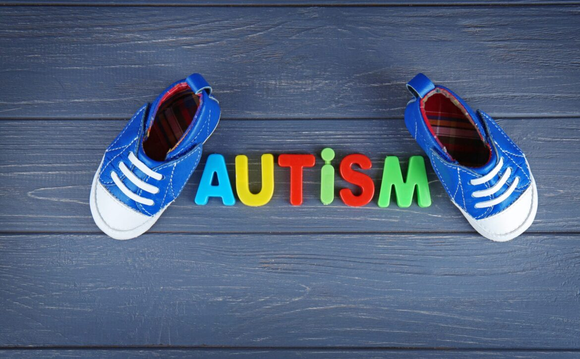 Word AUTISM with kids shoes on wooden background