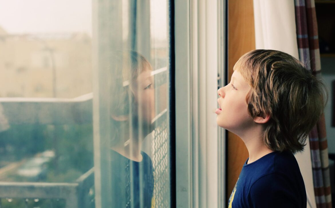 Cute 8 years old autustic boy looking at the rain